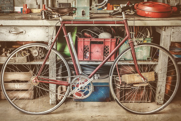 Poster de jardin Velo Vintage racing bycicle in front of an old work bench with tools