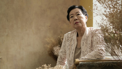 Asian elderly woman sit in beautiful luxury interior room tuscan vintage style