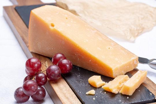 Piece of hard matured 3 years old dark yellow cheese close up