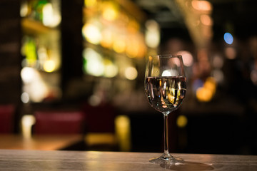A glass of white wine on the bar counter