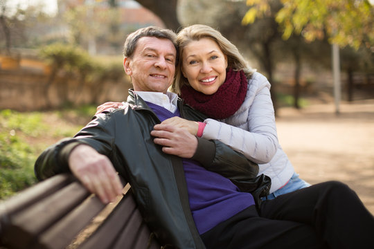 Mature family couple on a bench in the park in autumn day