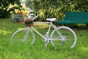 Rower biały z kwietnikiem, różowe kwiaty.