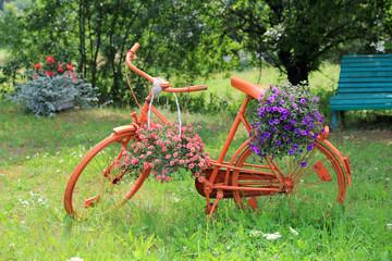 Rower pomarańczowy z kwietnikiem, różowe i fioletowe kwiaty.