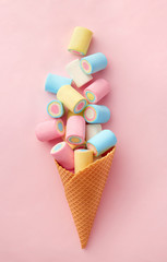 Marshmallow candy colorful assortment in an ice cream cone on a pink background viewed from above. Gummy candy variation. Top view