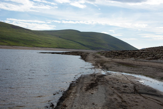Looking eastwards at a section of muddy road that is normally submerged under Loch Glascarnoch