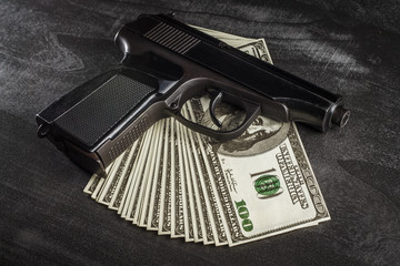 A pile of dollars and a gun on a dark wooden table