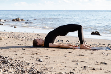 Young woman in black doing yoga on sand beach at sunrise