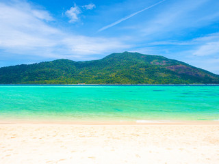 White sand beach and blue sea with mountain view in sunny summer day  for holiday or vacation concept.