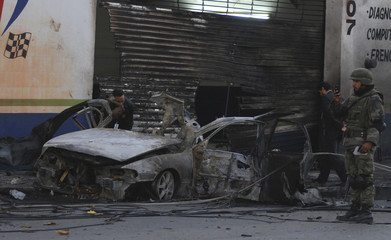 Police detectives inspect the site of a car bomb attack as a soldier takes pictures with his mobile phone in Monterrey