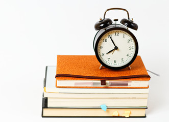 Back to school - black vintage classic clock on the stack of books on white background