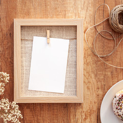 Frame mockup, white donut with colorful cupcakes, a string and white flowers in a vase on a wooden table