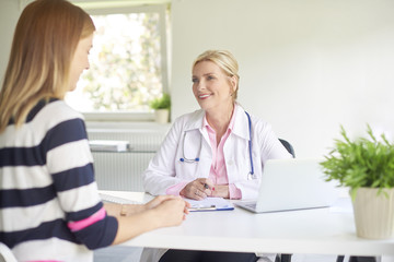 Smiling female doctor talking to woman at hospital