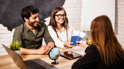 Young cute couple choosing a trip with agent sitting at the travel agency office with world map on the background