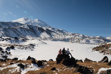 Two men and one woman look at the snowy mountain peak before the ascent