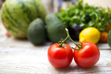 Fresh vine tomatoes with vegetables background including avocado and watermelon