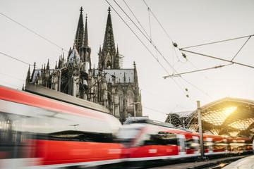 Regionalzug verlässt den Kölner Bahnhof Dom im Hintergrund