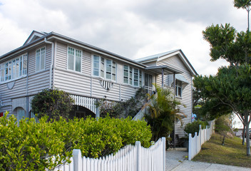 Typical Queensland house with tropical foliage and white picket fence on overcast day in Australia Fotobehang