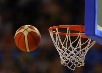 Basketball ball flies towards the basketball hoop on the background of the stands