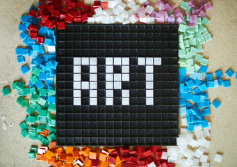 Top view of word ART laid out in white  square tiles over  black base with colored tiles scattered around, copy space background