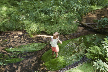Child cute blond girl playing in the creek. Gril walking in forest stream and exploring nature. Summer children fun. Children summer activities