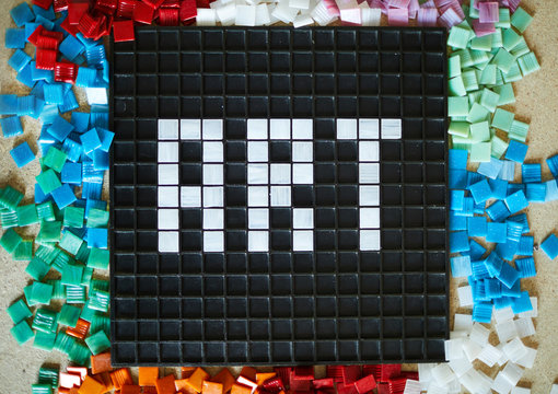 Above view of word ART laid out in white square tiles over black base with colored tiles scattered around