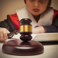 Portrait of serious child girl judge (lawyer) makes a decision. Humorous photo.(letter of law, strict law, justice concept)
