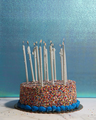 Sprinkle cake with many burning candles