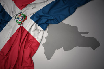 waving colorful national flag and map of dominican republic.