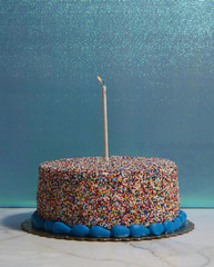 Sprinkled round cake with one burning candle on blue background.