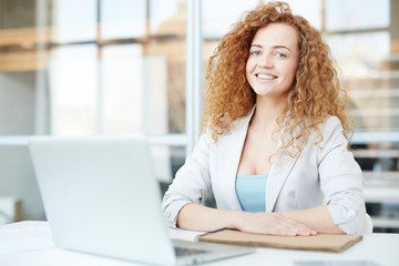Cheerful confident female manager with red curly hair sitting at table with laptop and looking at camera in modern office