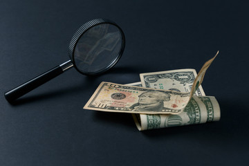 Magnifying glass and money on black background. Paper currency. Looking For Money. Concept of search. Close up
