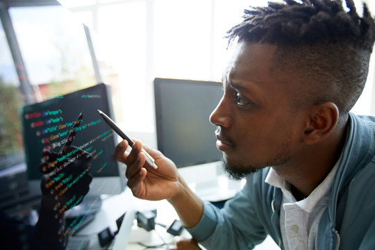 Serious concentrated young African-American programmer looking confused while learning coding language himself