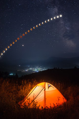 Camping tent in a mountain valley with total moon eclipse track