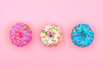 Three assorted donuts with pastel colored icing and sprinkles against a soft pink background....