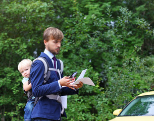 businessman reads documents or contract and looks on smartphone, his baby son in a sling on back