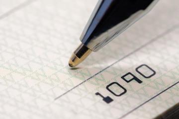 Up close macro of pen writing on a bank check