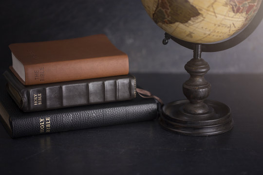 Stack of Bibles and a Globe on a Dark Background