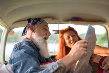 A hipster senior couple on vacation in a van, looking at a ma