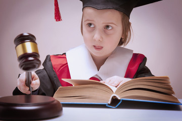 The letter of the law concept. Portrait of serious child girl judge (lawyer) makes a decision. Humorous photo.