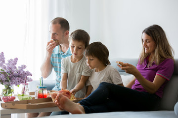 Beautiful young family with children, eating pizza at home and watching TV