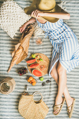 Aluminium Prints Picnic Summer picnic setting. Woman in linen striped dress and straw sunhat sitting with glass of rose wine in hand, fresh fruit and baguette on blanket, top view. Outdoor gathering or lunch concept