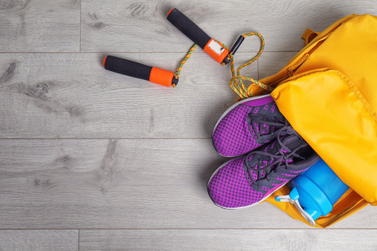 Sports bag with gym equipment on wooden background, top view
