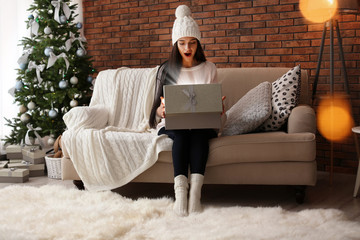 Beautiful young woman in hat opening gift box at home. Christmas celebration