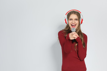 Young woman singing into microphone on color background. Christmas music