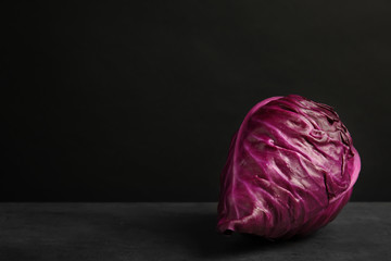 Pointed red cabbage on table against black background. Healthy food