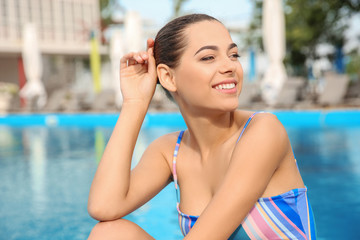 Young woman in bikini near swimming pool, outdoors