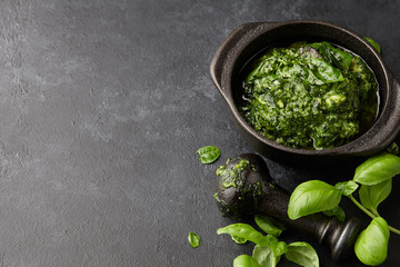 Basil pesto sauce with parmesan cheese, nuts, olive oil and garlic in black cast iron mortar, close up view
