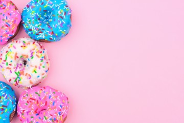 Side border of assorted donuts with frosting and sprinkles against a pastel pink background