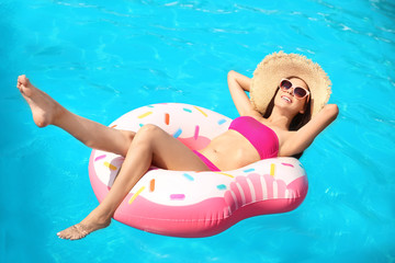 Beautiful young woman with inflatable ring in swimming pool