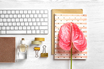 Creative flat lay composition with tropical flower and computer keyboard on wooden background